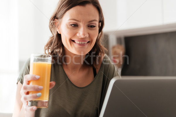 Close up picture of smiling casual woman drinking juice Stock photo © deandrobot