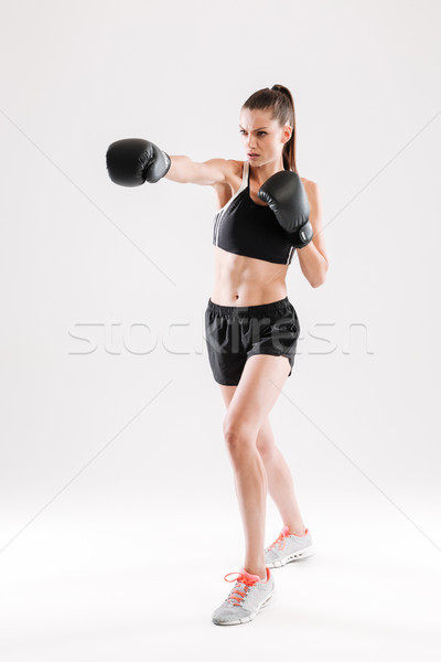 Full length portrait of a young motivated woman doing boxing Stock photo © deandrobot