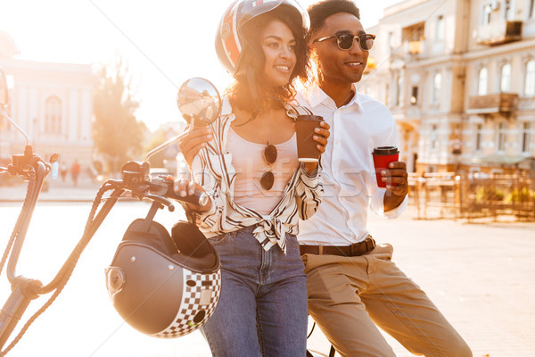 Happy young african couple drinking coffee while standing near motorbike Stock photo © deandrobot
