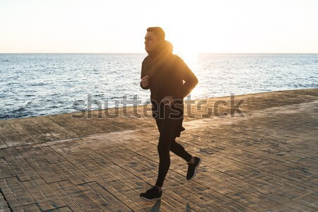 Slim fitness woman in sport wear running at the seaside Stock photo © deandrobot
