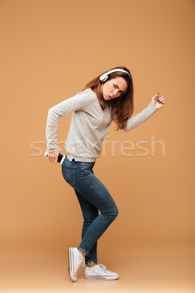 Full length portrait of funny attractive woman in casual wear ho Stock photo © deandrobot