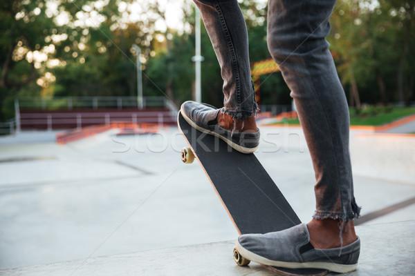 Young african man doing skateboarding Stock photo © deandrobot