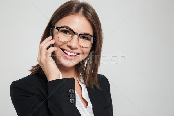 Close up portrait of an attractive cheery businesswoman Stock photo © deandrobot