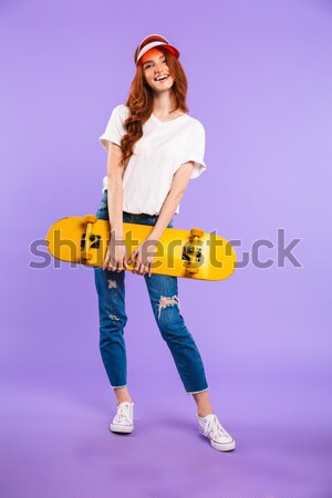 Young pretty woman in sunglasses holding skateboard Stock photo © deandrobot