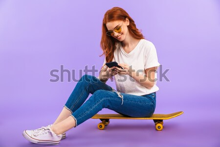 Young pretty woman sitting on skateboard isolated Stock photo © deandrobot