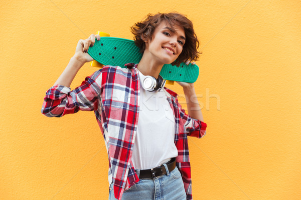 Happy pretty teenage girl holding skateboard on her shoulders Stock photo © deandrobot