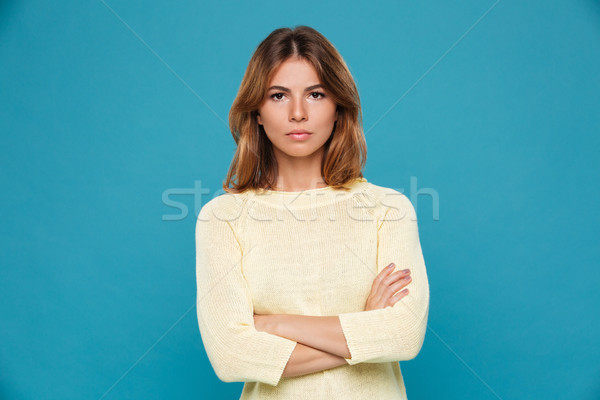 Stock photo: Serious young woman standing isolated over blue wall.