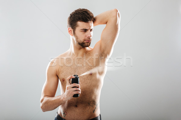 Portrait of handsome half-naked man spraying perfume over his mu Stock photo © deandrobot