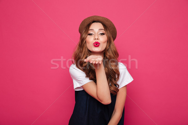 Beautiful brunette lady blowing an air kiss to camera isolated Stock photo © deandrobot