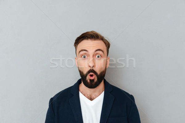 Shocked bearded man in business clothes looking at the camera Stock photo © deandrobot
