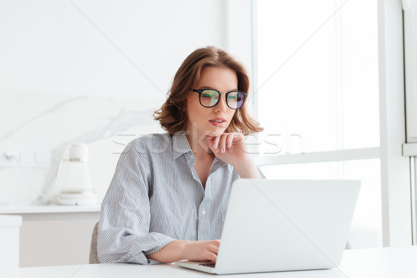 Charming businesswoman in glasses and striped shirt working with Stock photo © deandrobot