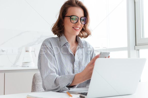 Portrait of charming woman in glasses and striped shirt using mo Stock photo © deandrobot