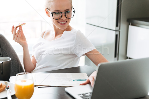 Cheerful lady eating bread with jam and using laptop Stock photo © deandrobot