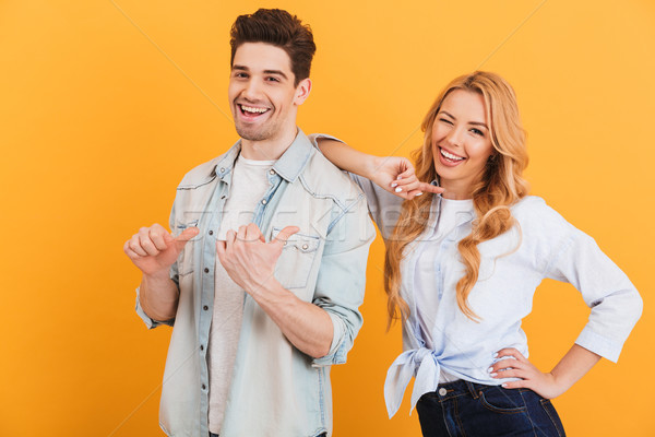 Photo of two young people in basic clothing smiling and pointing Stock photo © deandrobot