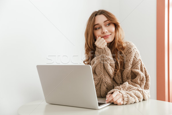 Image of pretty woman 20s in sweater with long brown hair lookin Stock photo © deandrobot