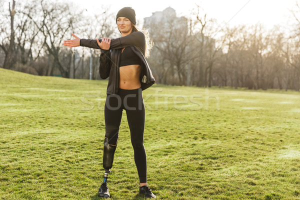 Image of beautiful handicapped sportswoman in tracksuit with pro Stock photo © deandrobot