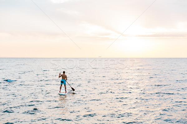 Handsome man kayaking on lake sea. Stock photo © deandrobot