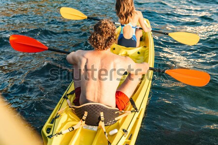Rear view of beautiful young couple kayaking Stock photo © deandrobot