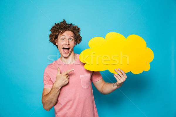 Photo of excited brunette man 20s with curly hair holding and po Stock photo © deandrobot