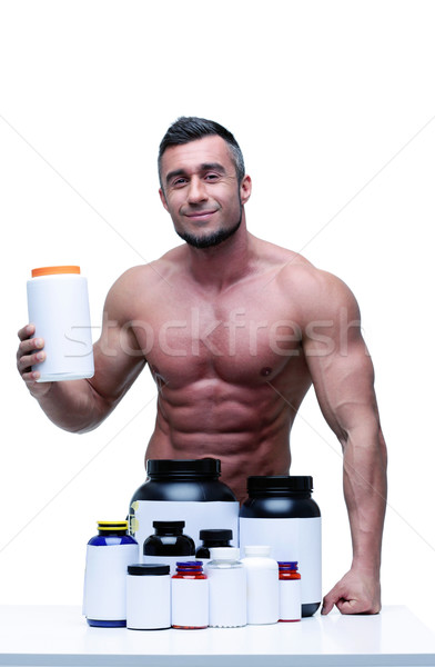 Portrait of a happy muscular man with sports nutrtion Stock photo © deandrobot