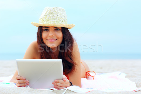 Young beautiful woman in swimming suit using her tablet on the beach Stock photo © deandrobot