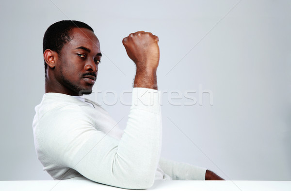Serious african man sitting at the table on gray background Stock photo © deandrobot