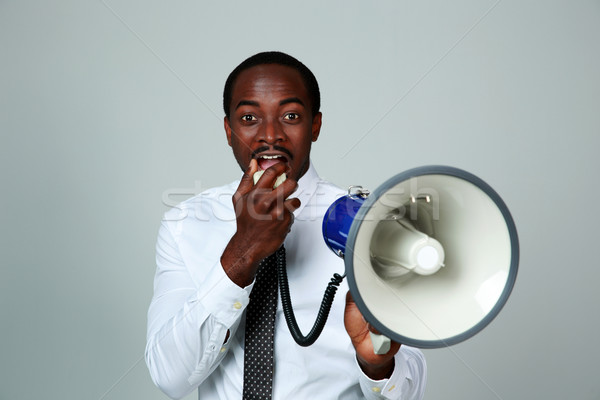 African man shouting through a megaphone on gray background Stock photo © deandrobot