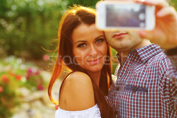 Couple taking self-portrait photos with mobile smart phone Stock photo © deandrobot