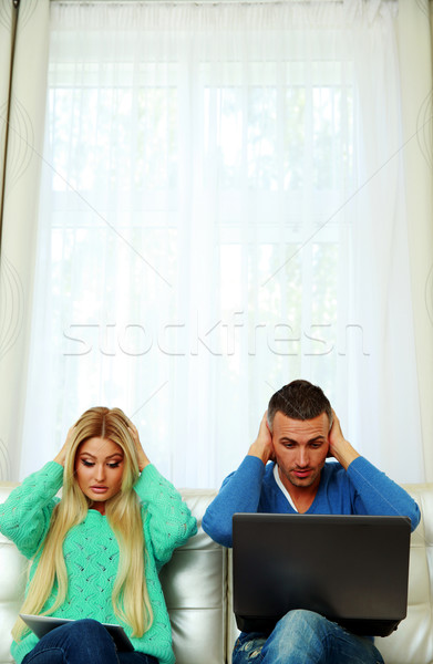 Scared couple sitting on the sofa with tablet computer and laptop Stock photo © deandrobot
