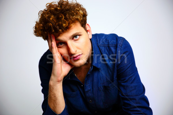 Handsome man with curly hair looking at the camera Stock photo © deandrobot