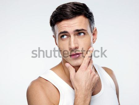 Pensive man looking away over gray background Stock photo © deandrobot