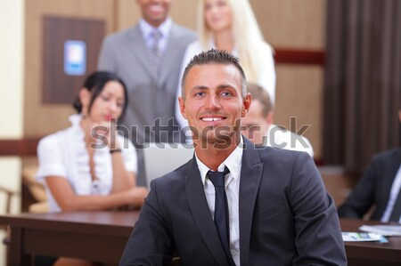 Handsome executive businessman with his team working behind Stock photo © deandrobot