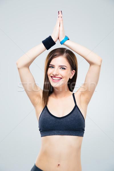 Smiling sporty woman making yoga exercises Stock photo © deandrobot