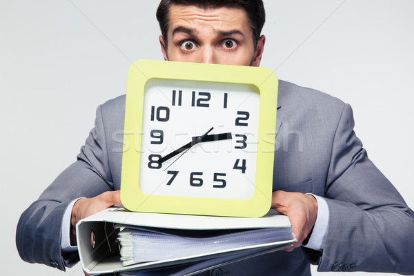 Businessman holding folders and clock Stock photo © deandrobot