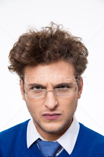 Mérges fiatal üzletember szemüveg néz kamera Stock fotó © deandrobot