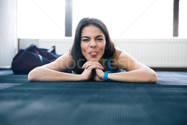 Woman lying on the floor and showing her tongue Stock photo © deandrobot