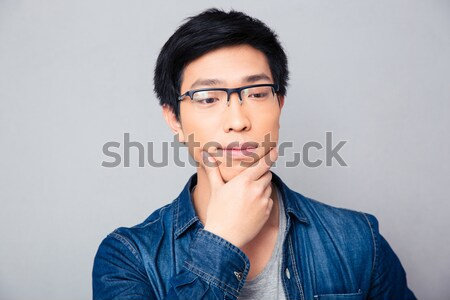 Portrait of a thoughtful asian man  Stock photo © deandrobot