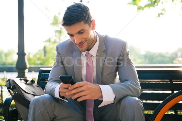 Happy businessman using smartphone outdoors Stock photo © deandrobot