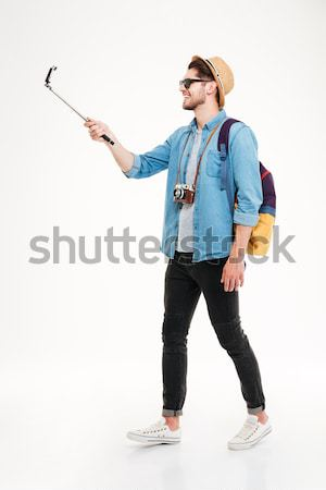 Smiling man making selfie photo with stick Stock photo © deandrobot