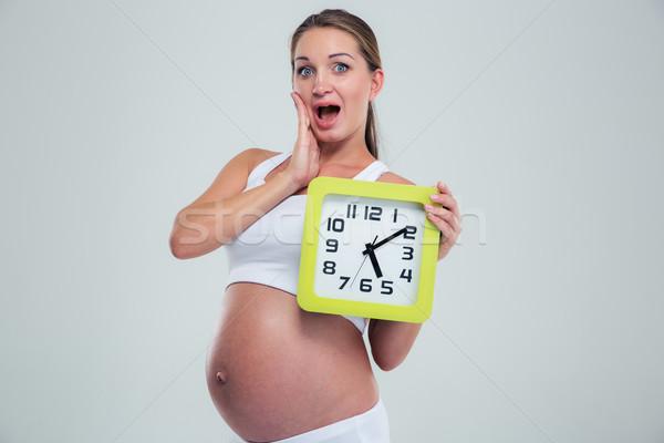 Stock photo: Amazed pregnant woman holding wall clock