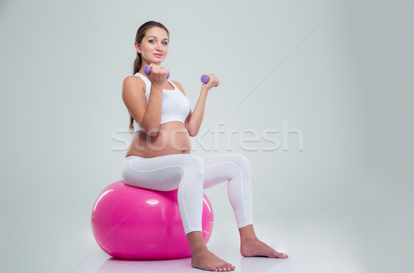 Woman sitting on a fitness ball and workout with dumbbells  Stock photo © deandrobot