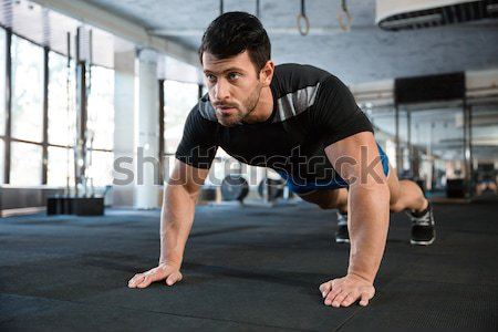 Handsome man doing push ups exercise  Stock photo © deandrobot