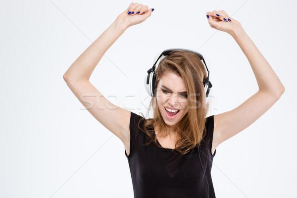 Cheerful woman listening music in headphones Stock photo © deandrobot