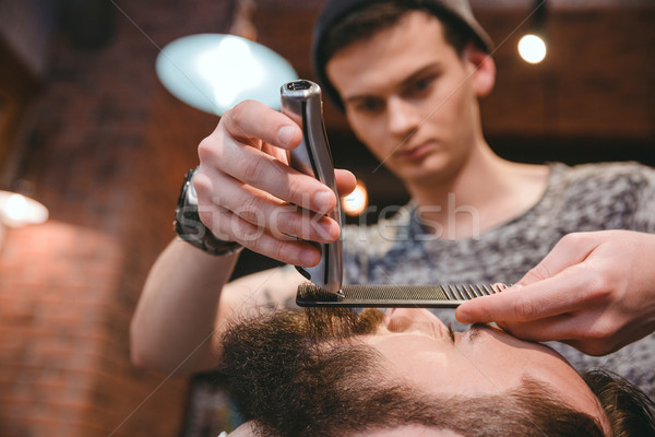 Concentrated barber making perfect beard to handsome bearded man  Stock photo © deandrobot