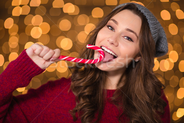 Beautiful happy woman eating candy cane over shining background Stock photo © deandrobot