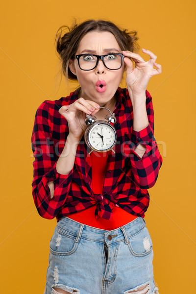 Funny surprised young woman in glasses holding alarm clock Stock photo © deandrobot