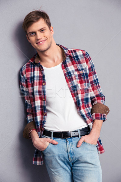 Smiling attractive young man in checkered shirt and jeans  Stock photo © deandrobot