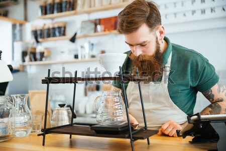 Barista pouring water on coffee ground with filter Stock photo © deandrobot
