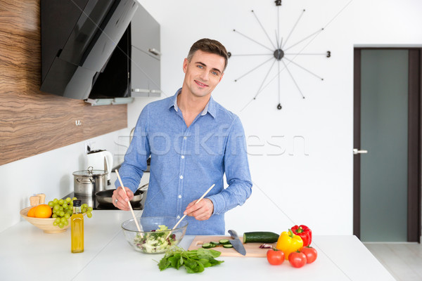 Attractive happy man making vegetarian salad on the kitchen Stock photo © deandrobot