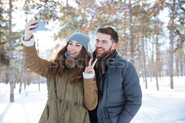 Woman making selfie photo with her boyfriend in winter park Stock photo © deandrobot